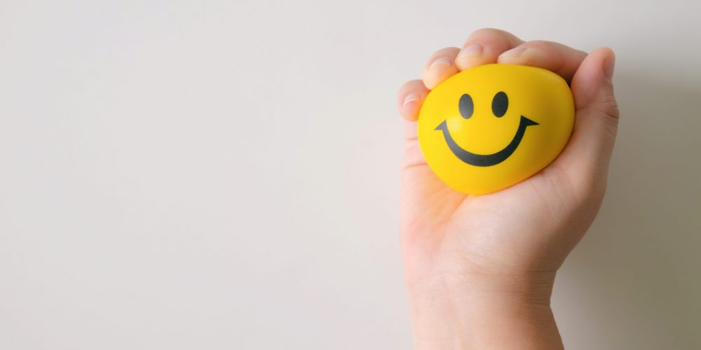 Hand squeeze yellow stress ball to relax.